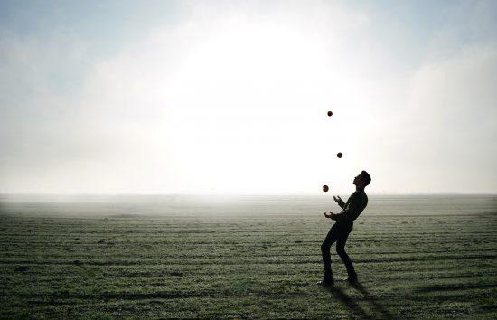 Man juggling balls on the beach