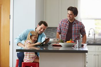 family in kitchen, girl looking at iPad