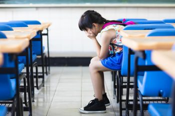 girl sitting on desk hands on knees