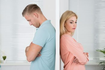 A man and woman on opposite sides of a door, after discovering an infidelity.