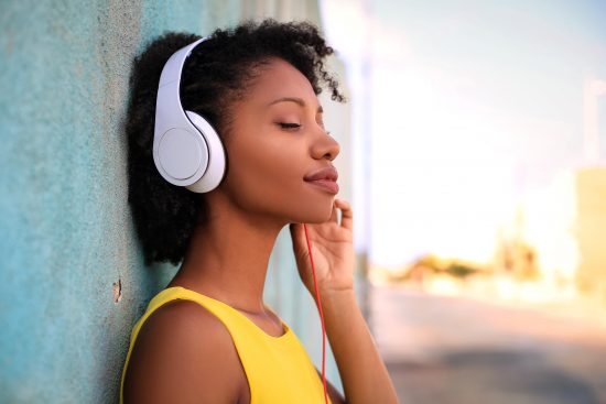 Smiling woman listening to soothing music with headphones