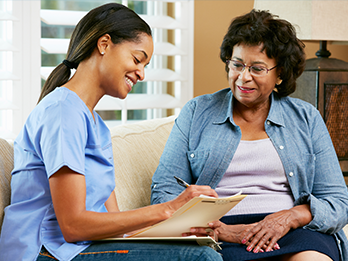 Health Home Care Coordinator completing paperwork with female patient at her home.