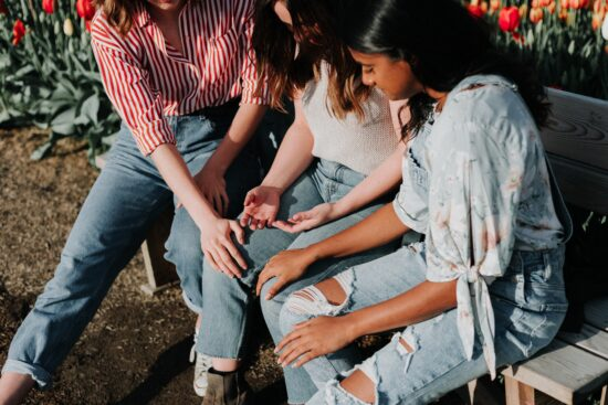 three women wearing blue denim sitting on bench outside, hands on each other in support