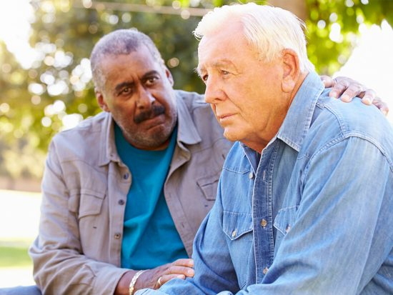 Man with hand on another man's arm, offering compassion and support during a conversation.