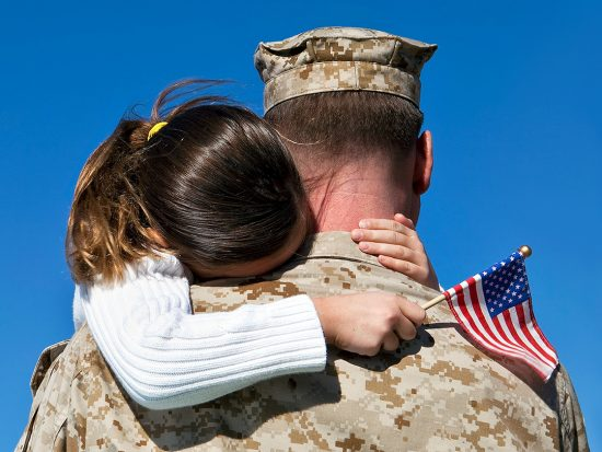 Soldier in fatigues ready for deployment hugging daughter with american flag