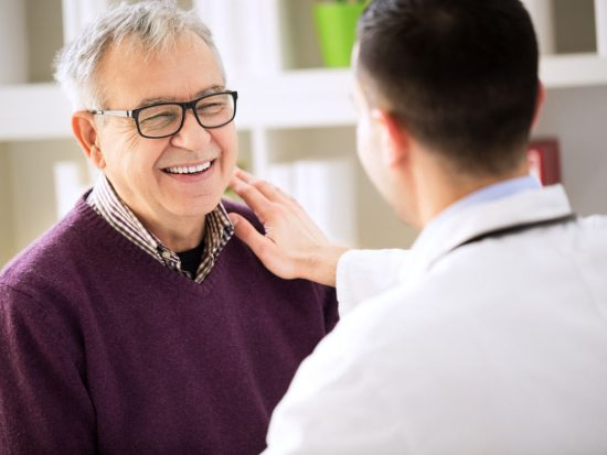 Doctor patting patient on shoulder in a friendly, reassuring way.