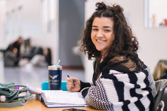 girl with dark hair sitting at desk smiling toward camera