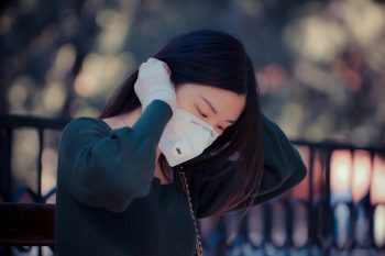 woman sitting outside putting on mask