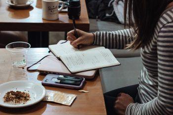 girl writing in journal in coffee shop