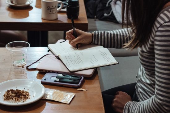 girl writing in journal in coffee shop