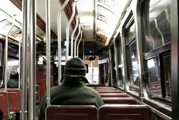 man dressed warm, alone in bus at night