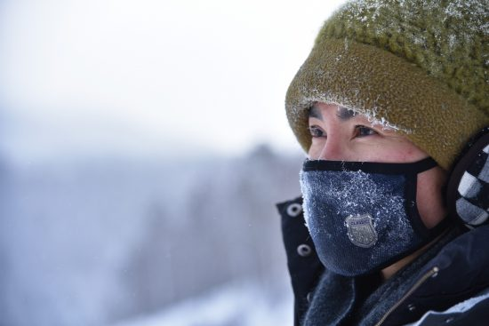 woman wearing green knit cap and blue mask in snow