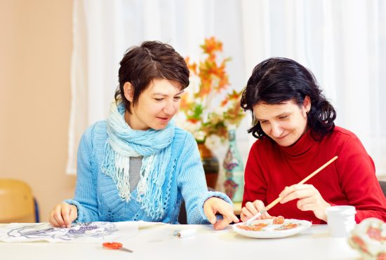 Art Therapist teaching adult woman how to paint