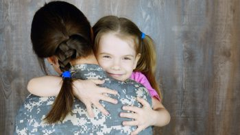 child and military mother hugging