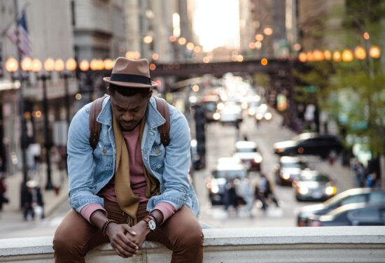 sad man wearing fedora and denim jacket looking down at folded hands outside in city