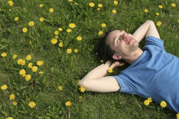 Man laying in grass, smiling