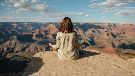 woman meditating on cliff with canyons in background