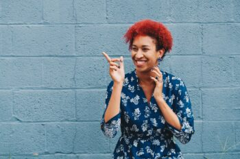black woman with red hair in front of blue wall smiling and pointing