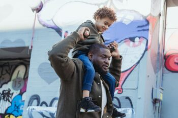 man holding son on his shoulders walking on the street