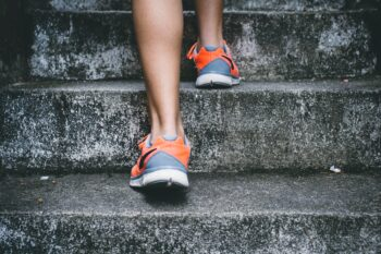 close up of orange and gray sneakers going up concrete steps
