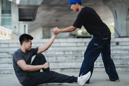 young man helping another young man get to his feet from the ground