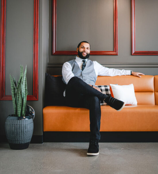 man wearing suit sitting on orange couch in room with gray walls