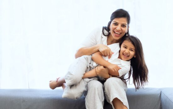 mother holding daughter sitting on gray couch wearing white, smiling
