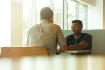 two young men sitting at table indoors
