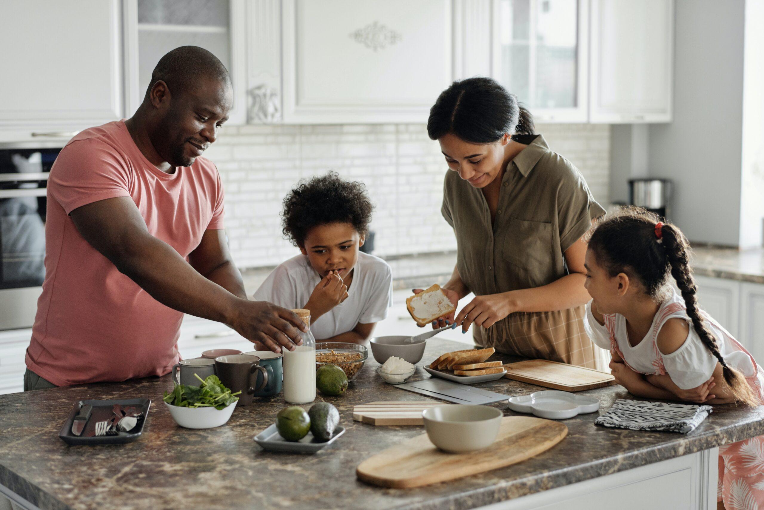 parents and children standing around kitchen island preparing food