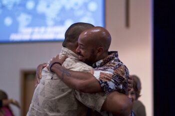 two men hugging inside, man in front smiling