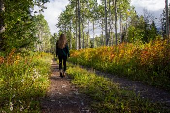 woman in jacket walking on pathway between grass and trees during daytime