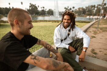man in black t shirt sitting next to man in white long sleeve shirt