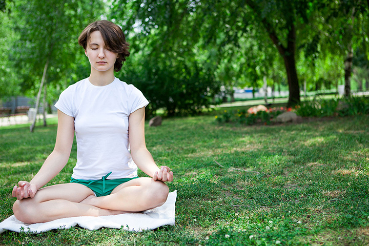 Woman meditating in a park to help control mood