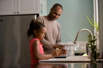 daughter washing hands with father guiding
