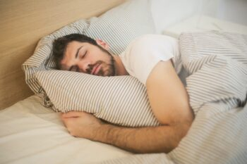 man holding pillow sleeping in bed