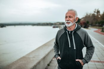 Portrait of a senior sportsman walking near the river in the city.