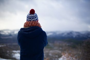 Person dressed warm staring into the wilderness