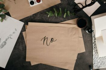 """piece of brown paper reading """"no"""" sitting on black table surrounding by other papers"""