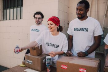 three people standing behind table with medical supplies wearing volunteer shirts