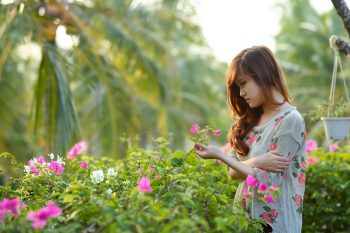 woman holding flower next to flower bushes with palm trees in background