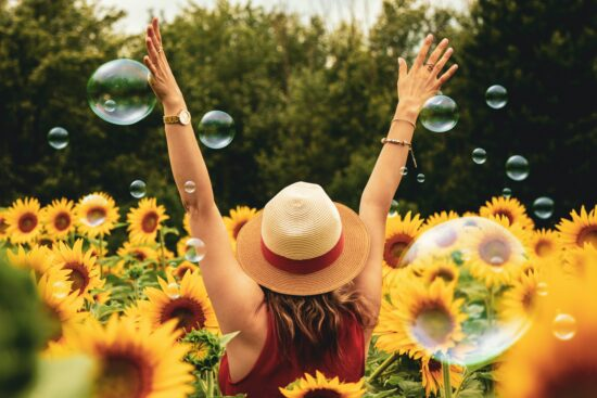 woman standing in sunflower field with arms raised and bubbles around