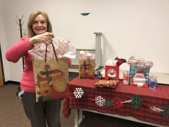Sunrise Rotarian Jean Ozols is pictured handing out Christmas gifts