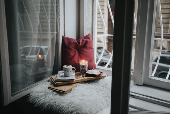 pillow, candle, mug and book on a wooden tray sitting in the window